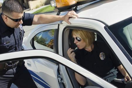 law enforcing: Police Officers Talking in Police Car LANG_EVOIMAGES