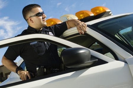 enforcing the law: Police Officer Leaning on Patrol Car