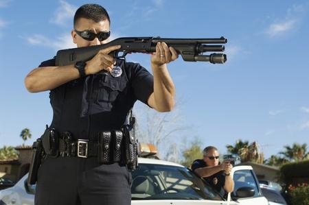 law enforcing: Police Officer Aiming Shotgun