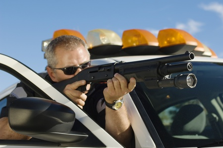 enforcing the law: Police Officer Aiming Shotgun