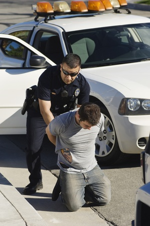enforcing the law: Police Officer Arresting Young Man LANG_EVOIMAGES
