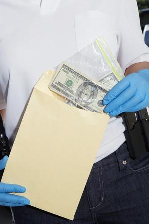 law enforcing: Police Officer Putting Money in Evidence Envelope