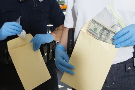30 to 35 year olds: Police Officer Putting Money in Evidence Envelope