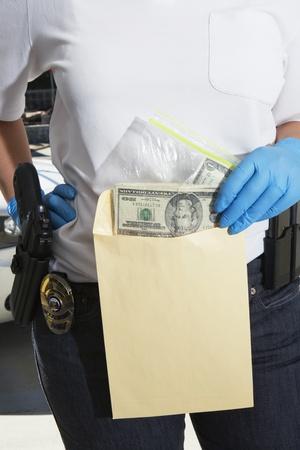enforcing: Police Officer Putting Money in Evidence Envelope
