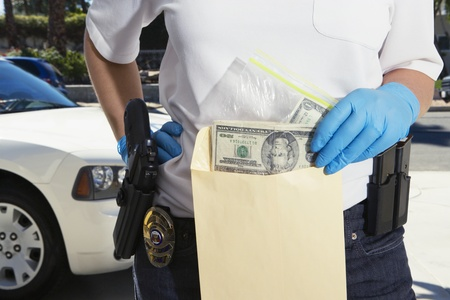 cropped out: Police Officer Putting Money in Evidence Envelope