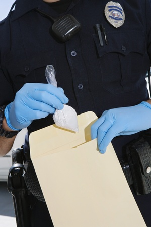 40 to 45 year olds: Police Officer Putting Cocaine in Evidence Envelope