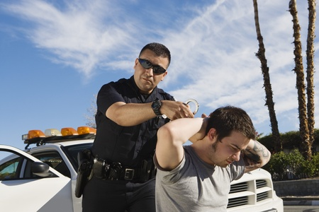 Police Officer Arresting Young Man Stock Photo - 12548105