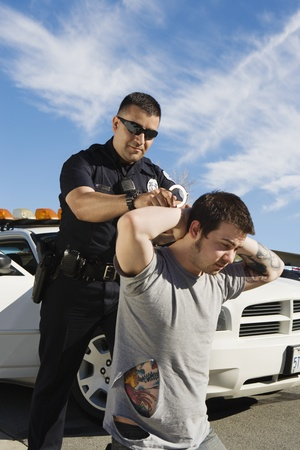 Police Officer Arresting Young Man Stock Photo