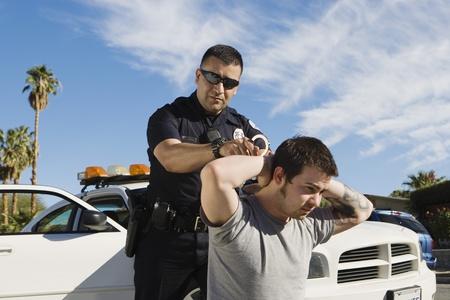handcuffed: Politieman Arrestatie Young Man