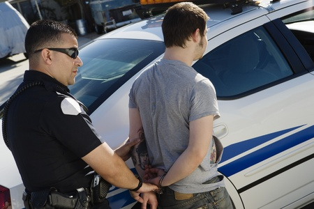 Police Officer Arresting Young Man Stock Photo - 12548108