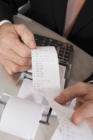 business roles: Businessman Looking at Calculator Paper