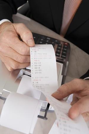 reciept: Businessman Looking at Calculator Paper