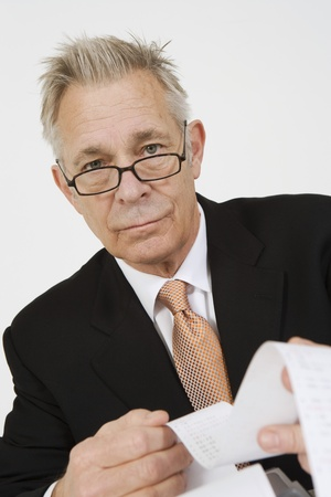 70 year old man: Businessman Looking at Calculator Paper