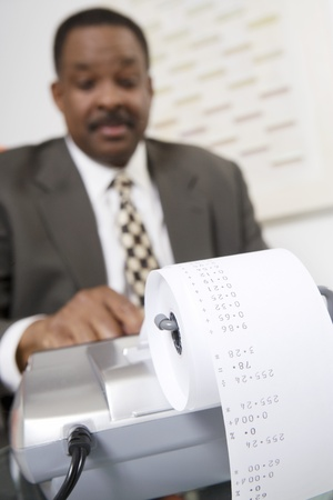 upper half: Businessman Using an Adding Machine