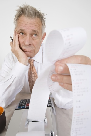 early sixties: Businessman Looking at Calculator Paper