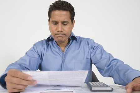 fortysomething: Man Reading Financial Document LANG_EVOIMAGES