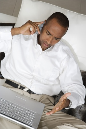 Businessman Using Laptop and Talking on Cell Phone Stock Photo - 12548237