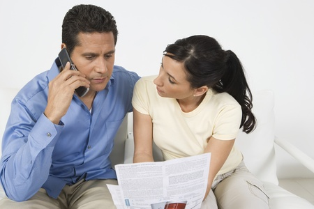 Couple Paying Bill on Phone Stock Photo - 12548246