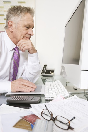 only one senior adult man: Businessman Working at Desk