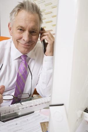 65 70: Businessman Working at Desk
