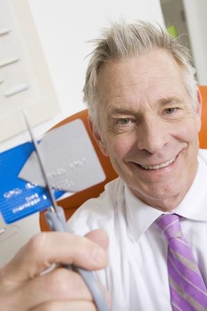 65 70 years: Businessman Cutting Credit Card