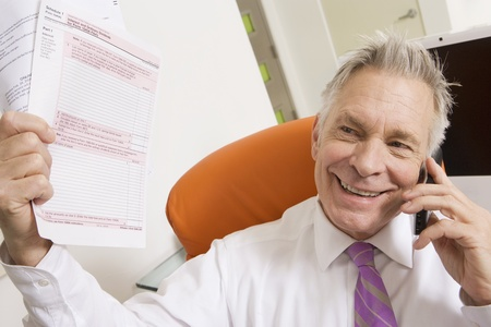 65 70: Businessman Holding Tax Forms LANG_EVOIMAGES