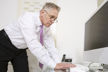 70 year old man: Businessman Working at Desk