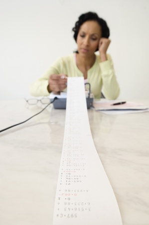 35 to 40 year olds: Woman Reading Adding Machine Tape LANG_EVOIMAGES