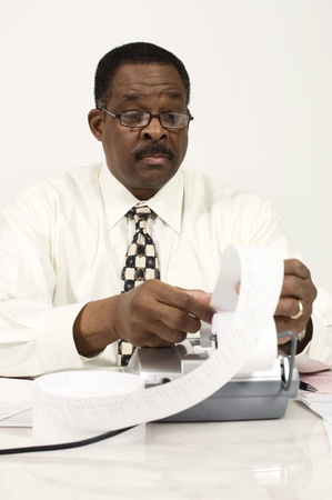 50 to 55 years old: Accountant Reading an Adding Machine Tape