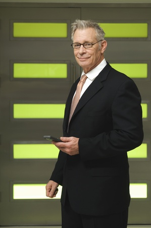 65 70 years: Senior Businessman Holding PDA
