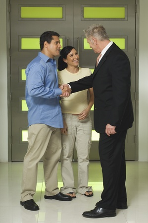 45 to 50 year olds: Businessman Shaking Hands with Couple