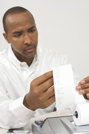 Man Looking at Calculator Tape
