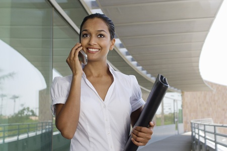 20 to 25 year olds: Businesswoman Talking on a Cell Phone LANG_EVOIMAGES