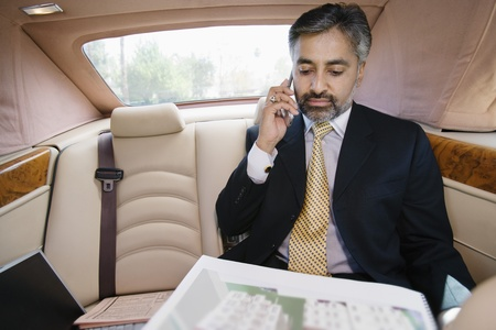 55 years old: Businessman Using Cell Phone in Private Car LANG_EVOIMAGES
