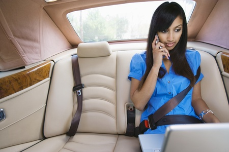 Young Woman Talking on Phone and Using Laptop in Car Stock Photo - 12548515