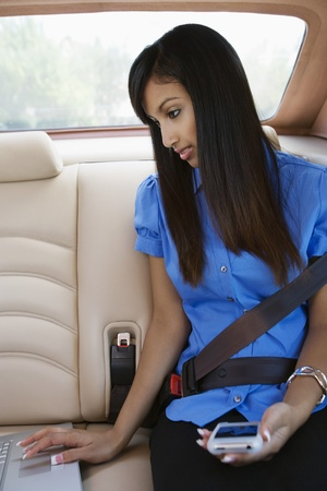 Young Woman Using Laptop and PDA in Car Stock Photo - 12548517
