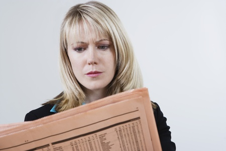 listings: Businesswoman Reading Stock Listings in Newspaper