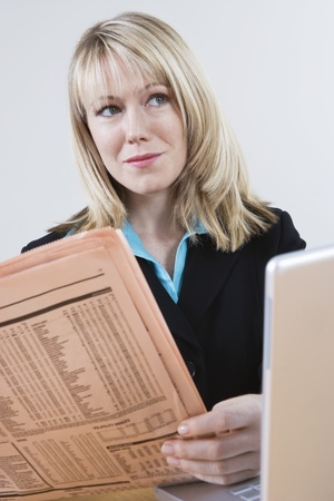 microcomputer: Businesswoman Reading Stock Listings in Newspaper