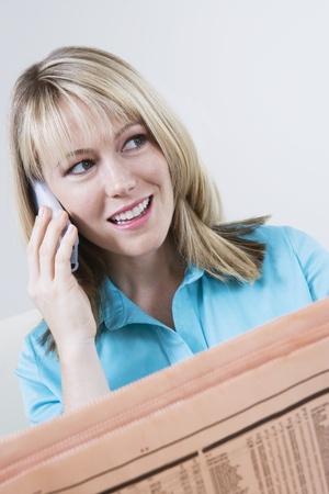 listings: Woman Reading Stock Listings in Newspaper