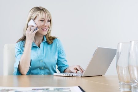 Woman Using Cell Phone and Laptop Stock Photo - 12548542