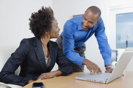 african business: Businesspeople Using Laptop During Meeting
