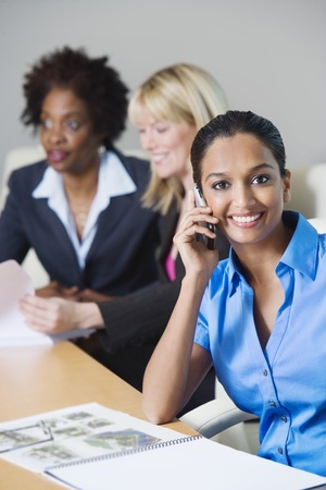 racially diverse: Businesswoman Using Cell Phone During meeting