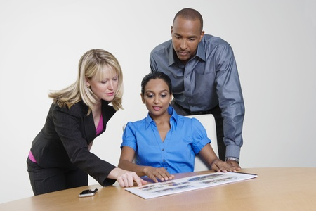 racially diverse: Businesspeople Looking at Booklet in Meeting LANG_EVOIMAGES