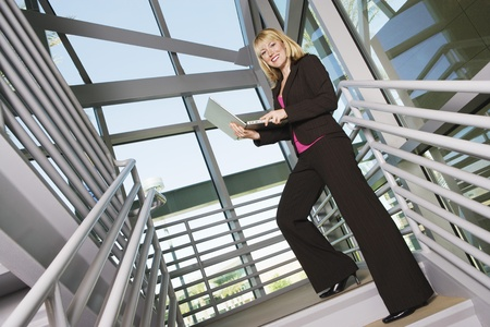 30 to 35 year olds: Businesswoman with Laptop on Stairs LANG_EVOIMAGES