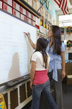 Schoolgirl and teacher standing in front of projection screen Stock Photo - 12592411