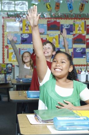Three pupils with raised hands Stock Photo - 12592418