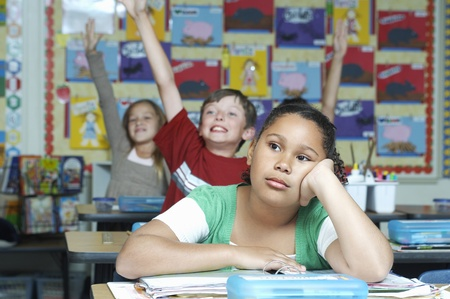 Three pupils in classroom two with raised hands one pensive Stock Photo - 12592419