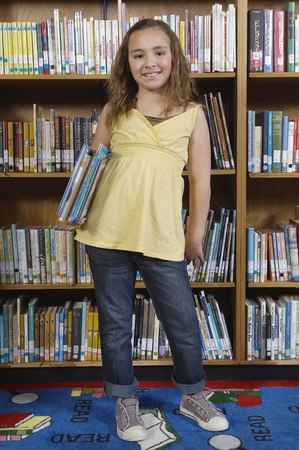School girl holding books in library portrait Stock Photo - 12592445