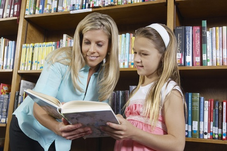 School girl reading book with teacher in library Stock Photo - 12592446