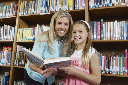 School girl and teacher holding book in library portrait Stock Photo - 12592447